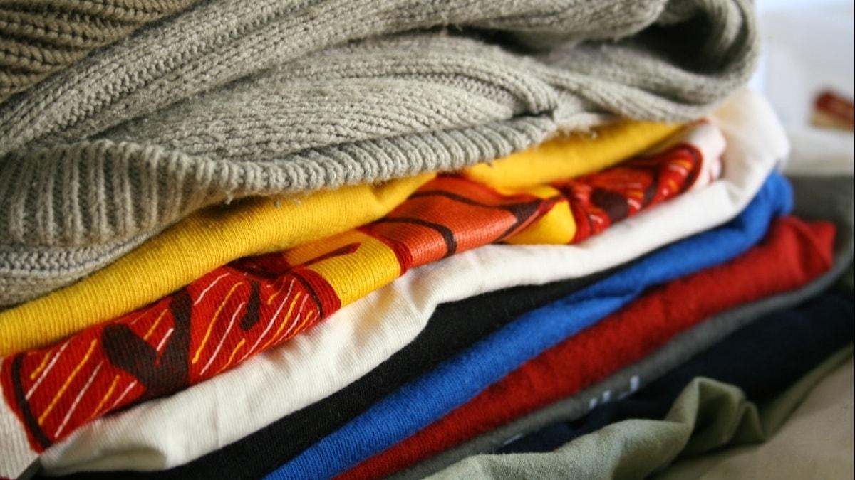 En hög av ihopvikta kläder i blandade färger.