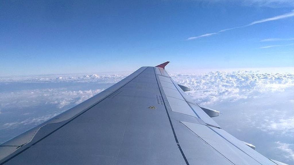 Flygplansvinge sedd inifrån ett flygplan som är i luften