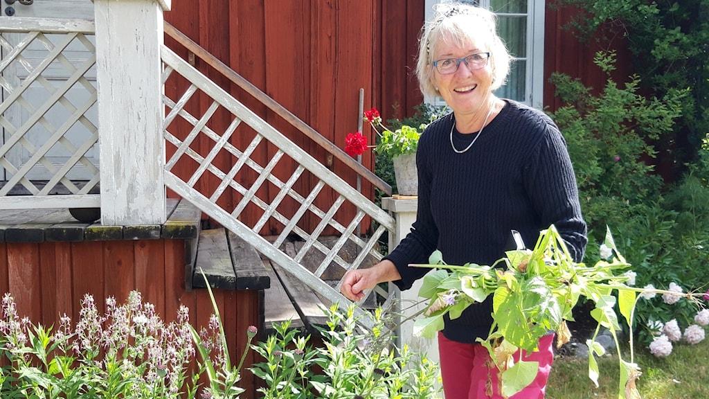 Kvinna framför rödfärgat hus med bortrensad parksallat i handen.