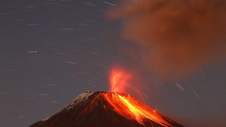 Vulkanutbrott med lysande lava och ett rökmoln.