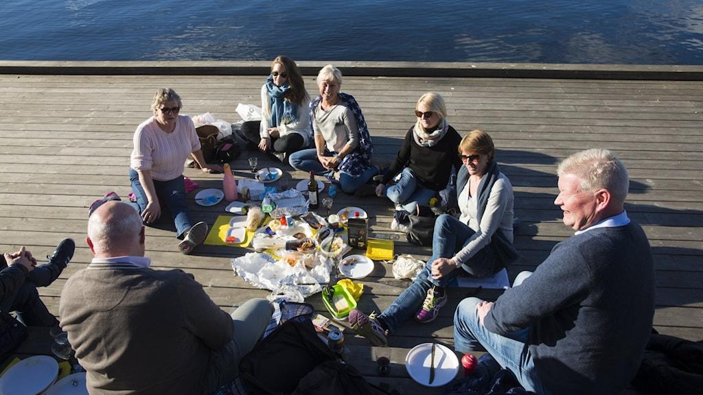 Flera personer sitter på en solig brygga och äter picknick.