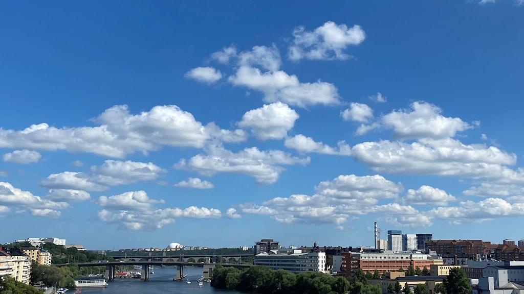 En blå himmel med stackmoln över en stadssilhuett i soligt väder, och vatten i förgrunden.