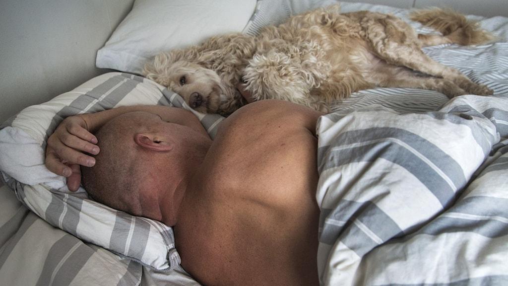 En man ligger i en säng vänd med ryggen mot kameran. Bredvid honom ligger en lurvig hund och sover.