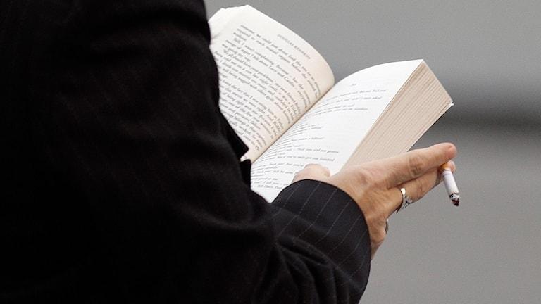 Kvinna läser bok och röker samtidigt