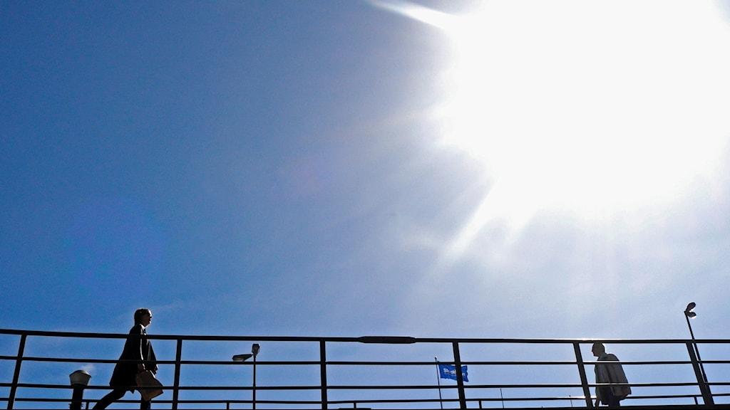 sol över bro med promenerande människor