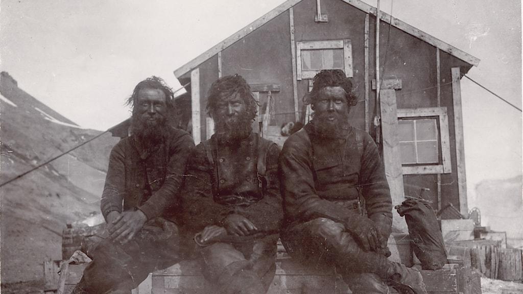Svartvit bild på tre mycket skäggiga och mörkklädda sittande män framför ett trähus.