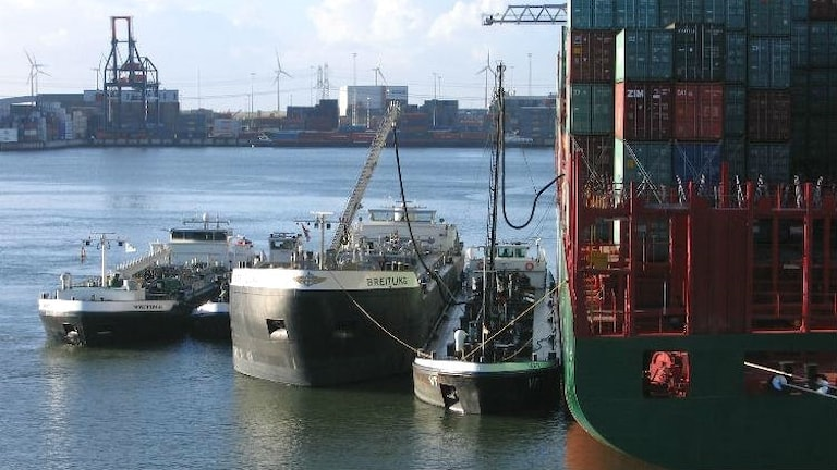 Ett containerfartyg ligger i en hamn och tankas.