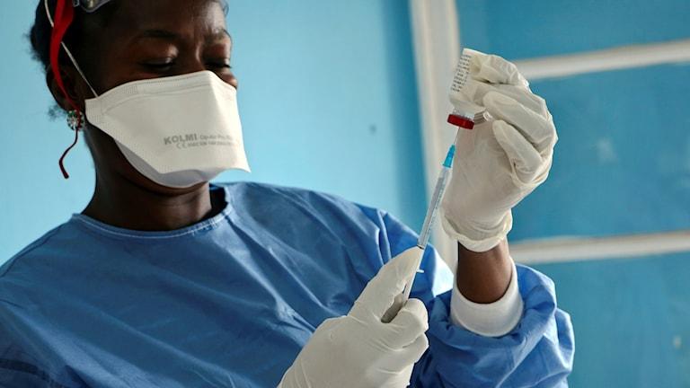 Person med vaccinspruta och munskydd.