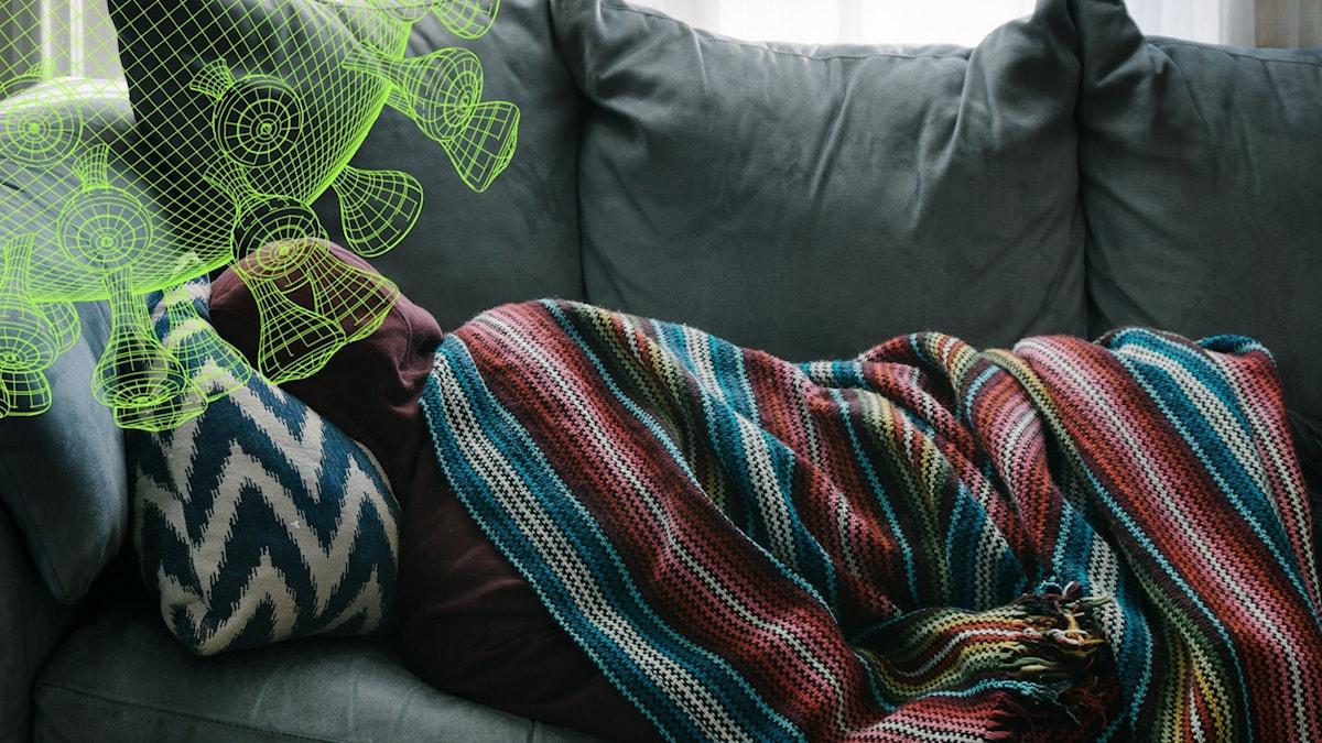 En person som ligger på en soffa med en filt över sig.