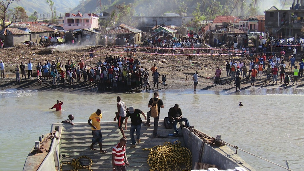 En båt med förnödenheter anländer till nödställda i Haiti efterjordbävningen 2010. Längst med en strandkant står flera människor och väntar på båten. Bakom den ligger flera raserade hus.