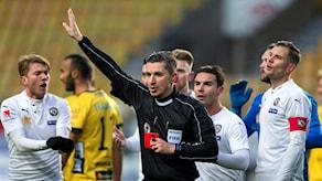Domare håller upp handen för att tysta upprörda spelare, i den andra handen håller han ett rött kort.