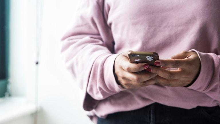 Ung kvinna med rosa tröja håller en smartphone i händerna.