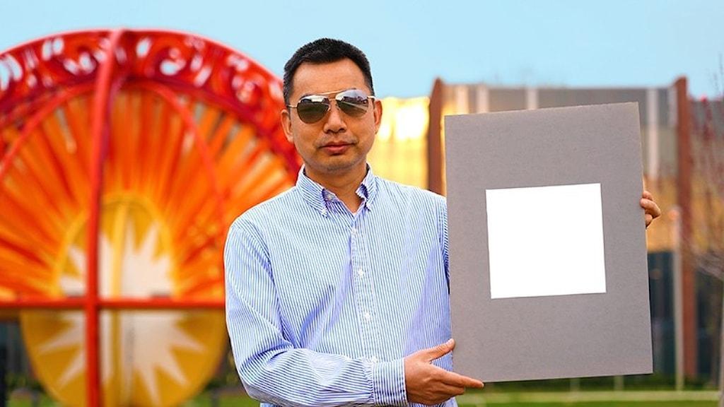 Xiulin Ruan, maskiningenör och professor vid Purdue Universitet, håller upp ett exempel på den vitaste färgen någonsin.