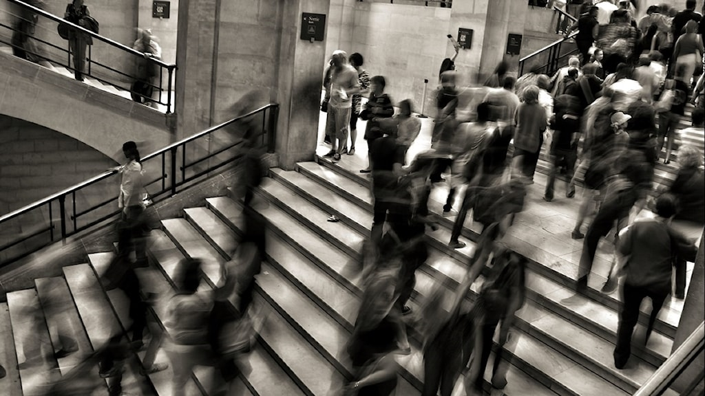 Massor av människor rusar upp och ned för en stor trappa.