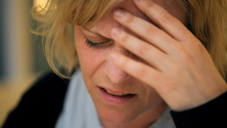 Kvinna som uttrycker smärta och har handen i ansiktet.