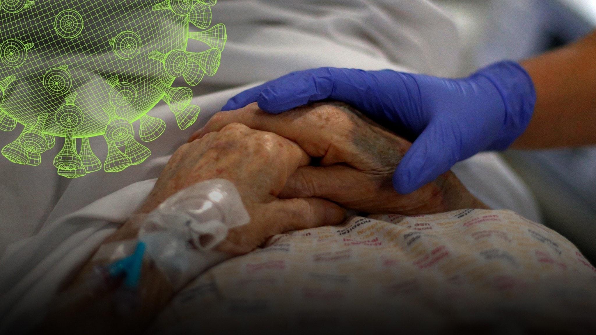 hand med skyddshandske ligger ovanpå en gammal persons hand.