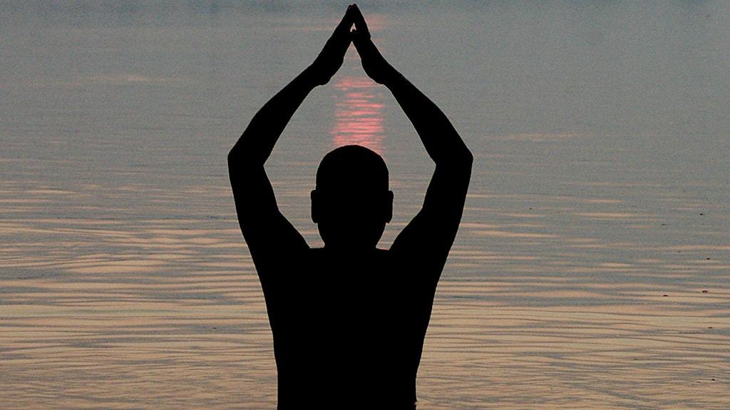 Person som mediterar vid vatten.