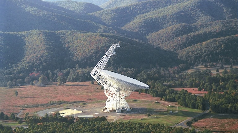 Ett stort teleskop omgiven av gröna kullar