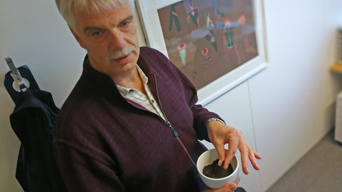 Willem Goedkoop håller i en liten skål med nedsmulade musslor.