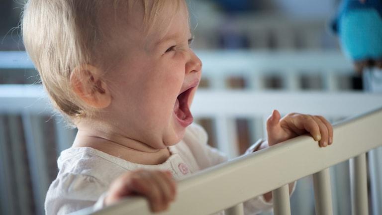 Bebis står upp i spjälsäng