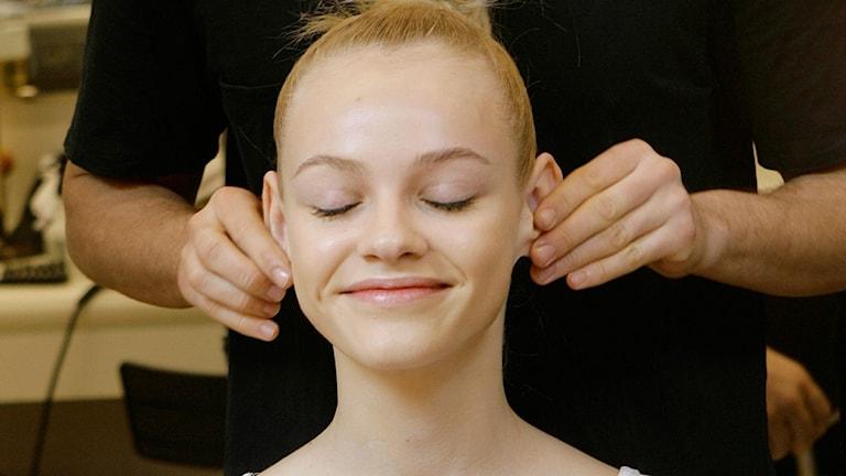 En leende blond tjej blundar och får öronmassage.