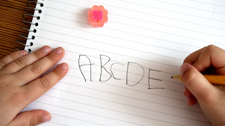 En barnhand skriver A, B, C, D, E.