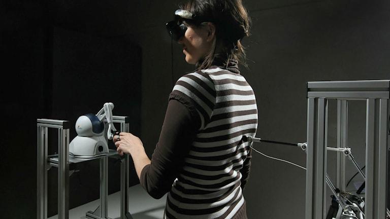 Försöksperson håller i en robot samtidigt som en robot petar i ryggen.
