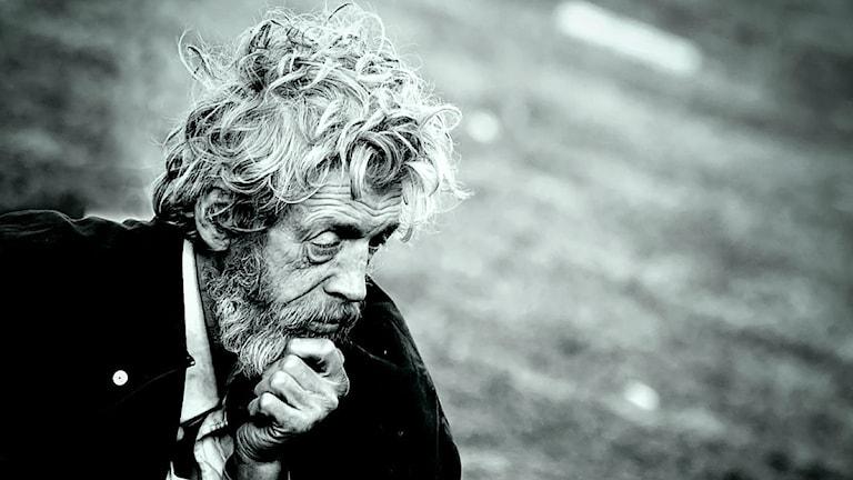 En man med skägg och rufsigt hår håller sig tankfullt för hakan.