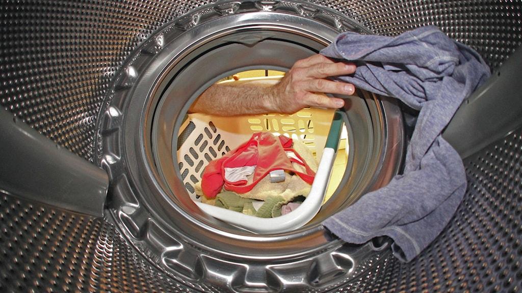 Inifrån en tvättmaskin syns en hand sträcka sig in efter ett klädesplagg