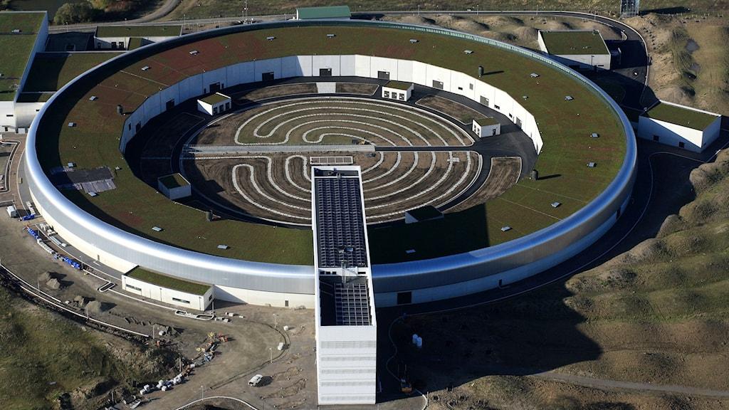 Anläggningen syns från flygperspektiv snett uppifrån. Den är cirkelformad, byggnaden är cirkelns omkrets.
