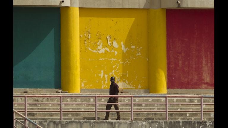 Man framför mur målad i Malis färger. Foto Rebecca Blackwell/AP/TT