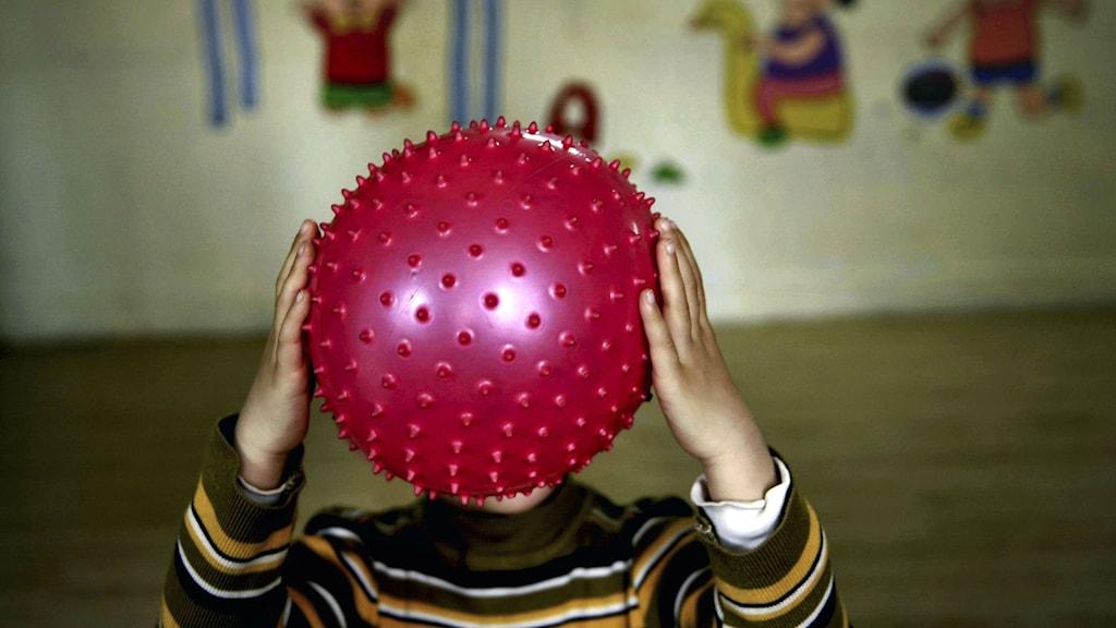 En autistisk pojke leker med en plastboll. En ny studie visar att syskonpar från samma familjer kan ha olika riskfaktorer i sina gener för att utveckla autism. Foto: AP