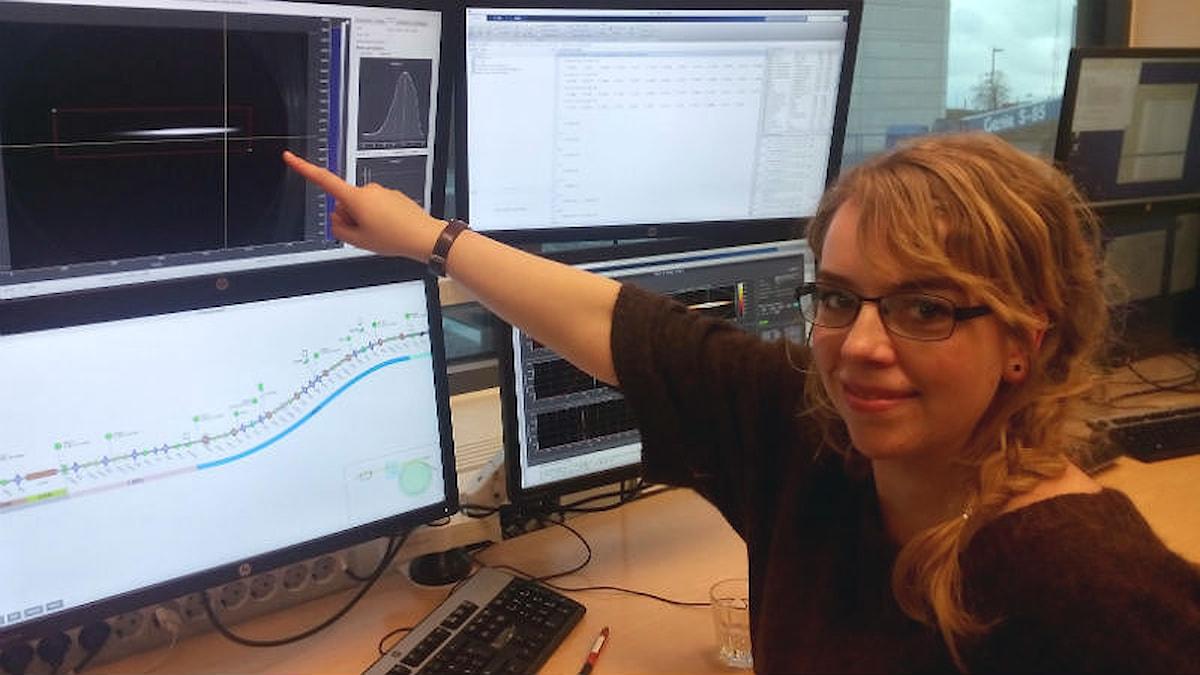 Sara pekar på en mörk skärm där ett vitt streck syns.