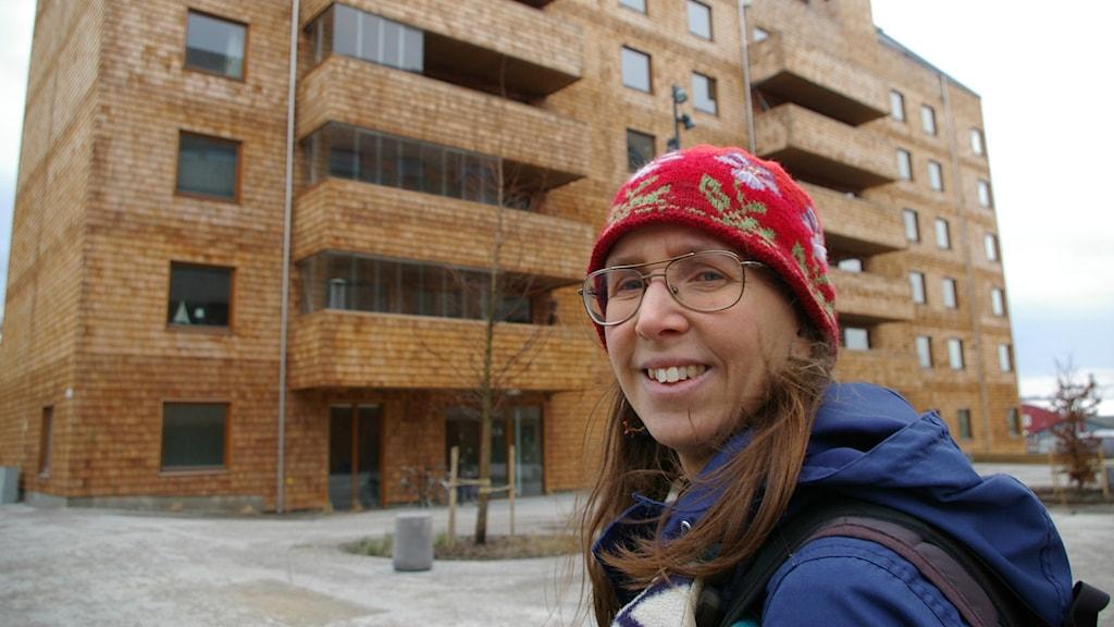 Tove Malmqvist vid ett av åttavåningshusen helt i trä. Foto: Björn Gunér/SR