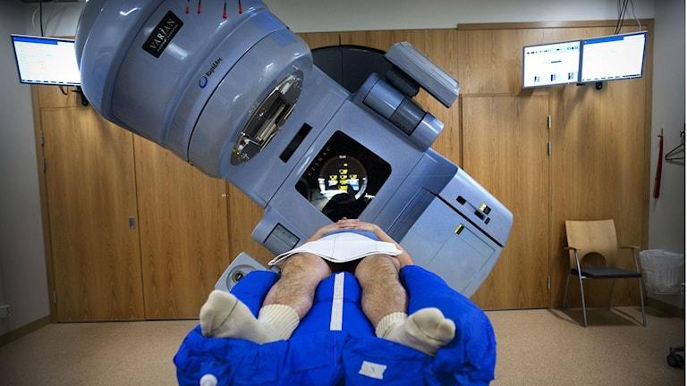 En man ligger i en strålningskanon. Det är stor maskin som kan undersöka kroppen.