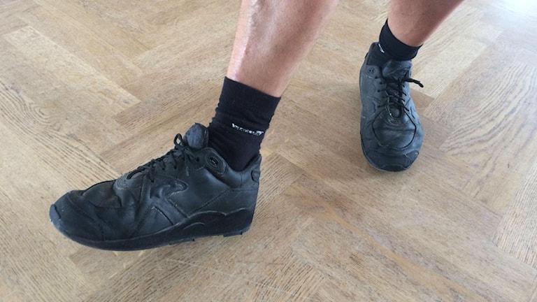 Fötter iklädda svarta gympaskor.