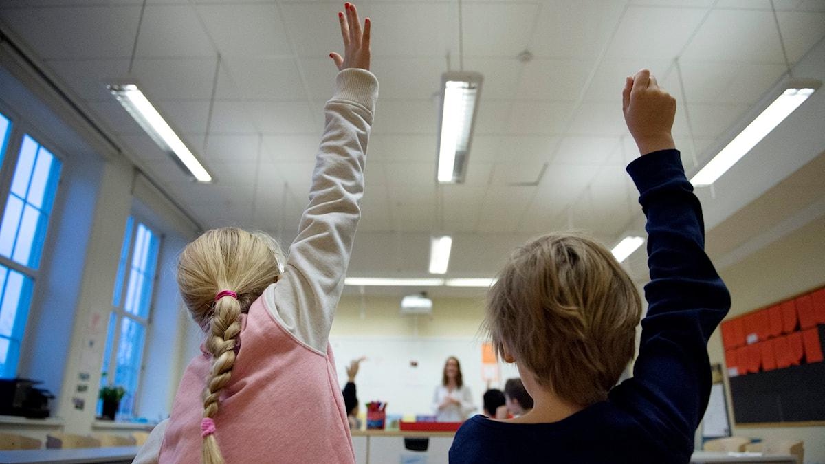 Tyttö ja poika viittaavat luokassa ala-asteella.