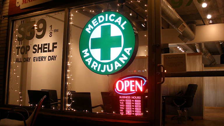 Ett skyltfönster med en logo där det står Medical Marijuana, och en lysande öppetskylt. Foto: O'Dea/Wikimedia Commons CC BY-SA 3.0