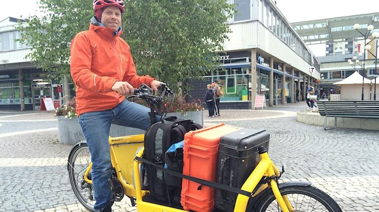 Man sitter på sin el-last-cykel, full med bagage. Foto: Pelle Zettersten/SR