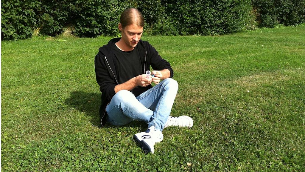 Masterstudenten Markus Hiltunen sitter i skräddarställning i gräset vid en häxring, med frystorkade nejlikbroskskivlingar i handen. Foto: Michaela Lundell/SR