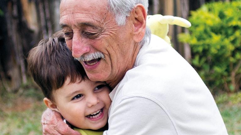 Äldre man kramar liten pojke, båda ser glada ut. Foto: Thomás/Flickr (CC)