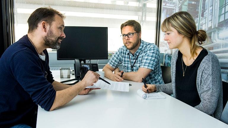 Tre personer samtalar i ett kontorsrum