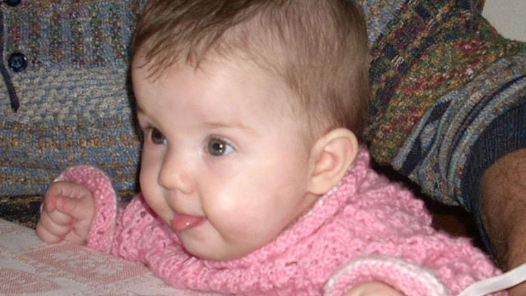 Sju månader gammal bebis som räcker ut tungan.