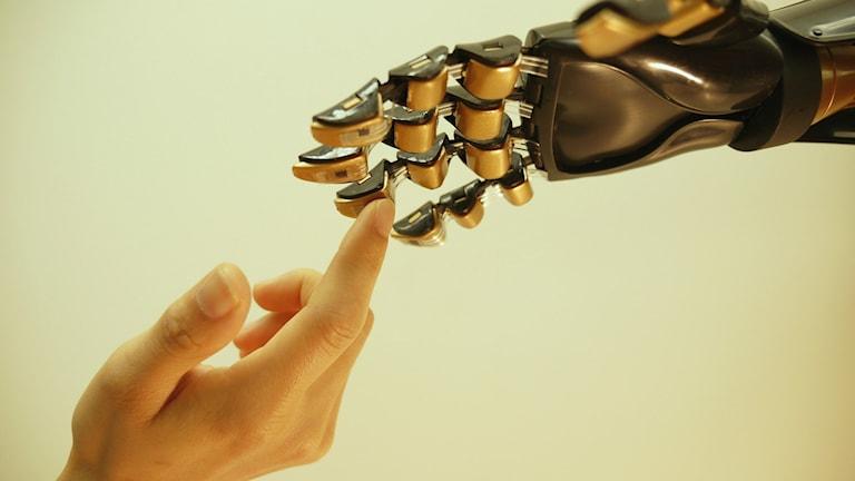 Mänsklig hand vidrör robothand