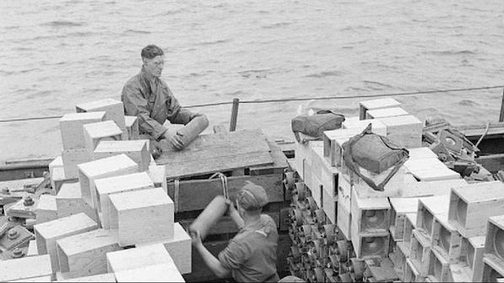 två soldater med tubliknande behållare