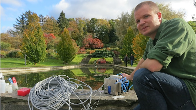 Henrik Nilsson sitter vid en damm med utrustningen bredvid sig. Foto: Christian Wurzbacher