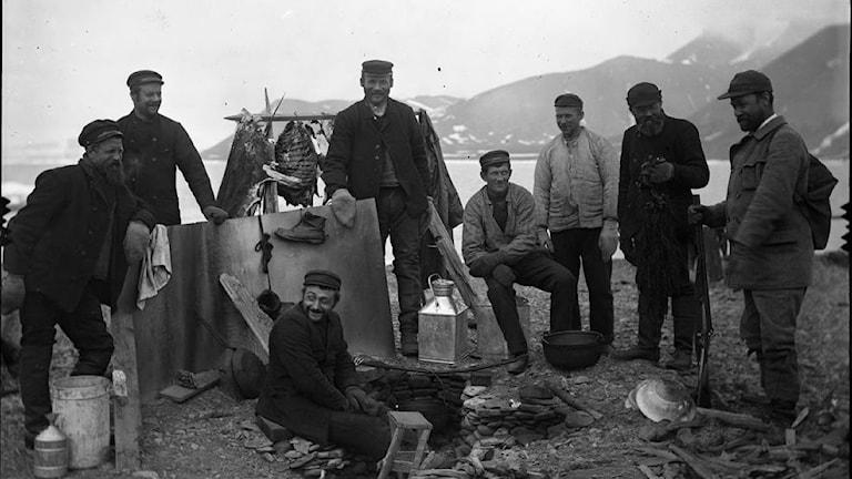 En grupp män med berg i bakgrunden