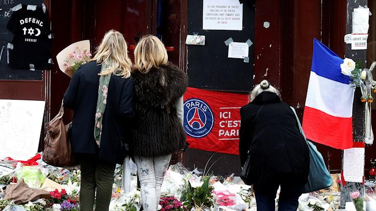 Människor vid minnesplats för offren i Paris. Foto: TT