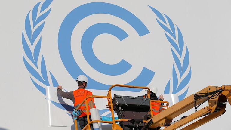 Man i lyftkran monterar skylt på fasaden till byggnaden där klimatmötet i Paris ska hållas. Foto: Christophe Ena/TT