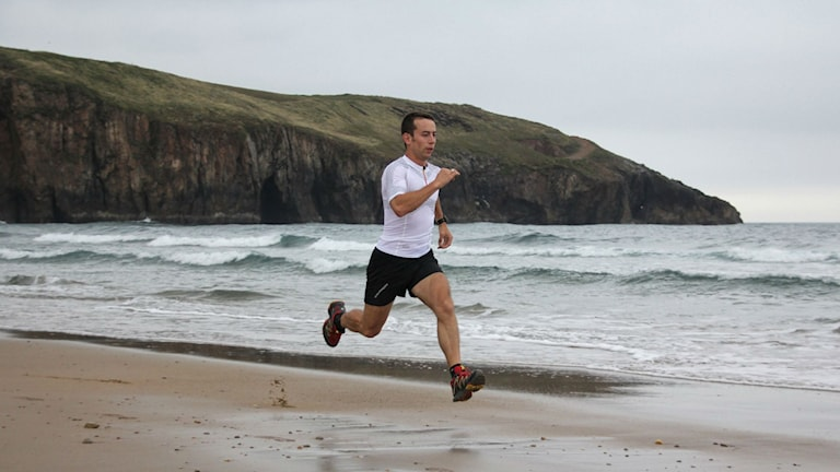 Man springer med långa, spänstiga kliv över strand. Foto: Amadfer CC BY-SA 3.0